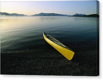 A Yellow Canoe On The Shore Of A Calm Canvas Print by Michael Melford