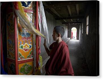 A Young Monk Spinning A Prayer Wheel Canvas Print by David Evans
