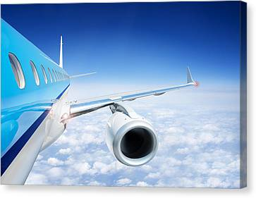 Airliner In Flight Above The Clouds Canvas Print by Corepics