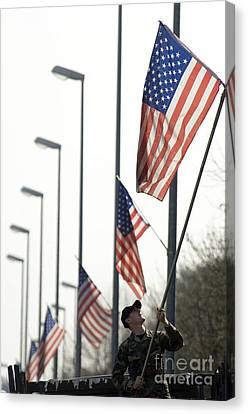 Airman Posts A New Flag On The Main Canvas Print by Stocktrek Images