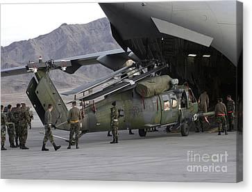 Airmen Load An Hh-60 Pave Hawk Canvas Print by Stocktrek Images
