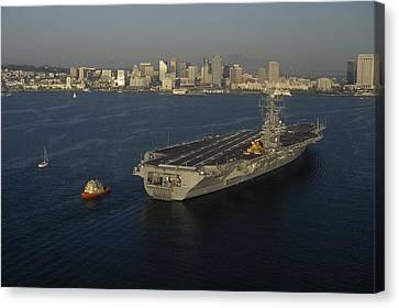 An Aircraft Carrier With The Skyline Canvas Print by Phil Schermeister