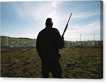 An Armed Guard Watches Over Inmates Canvas Print by Bill Curtsinger