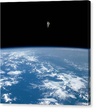 An Astronaut Propelled Above The Earth Canvas Print by Nasa
