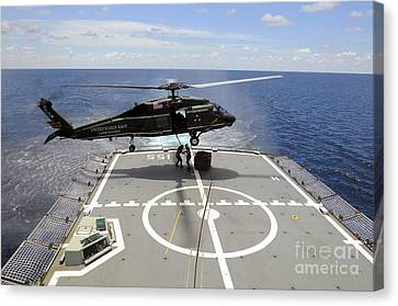 An Sh-60f Sea Hawk Helicopter Lowers Canvas Print