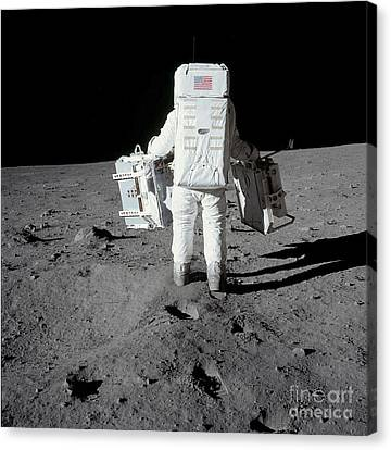 Astronaut Carrying Equipment Canvas Print by Stocktrek Images