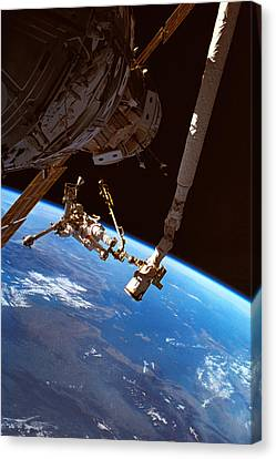 Astronauts Working On A Satellite In Space Canvas Print by Stockbyte