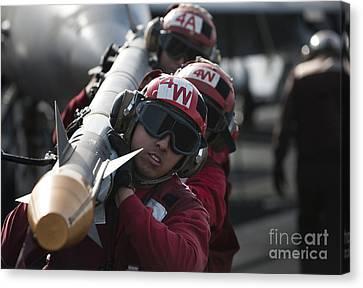 Aviation Ordnancemen Carry An Canvas Print by Stocktrek Images