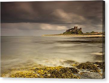 Bamburgh Castle Under A Cloudy Sky Canvas Print by John Short