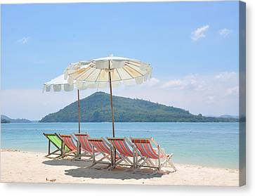 Beach Chair And Umbrella On Beach Canvas Print by Eustaquio Santimano