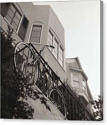 Bike Locked On Fence Against House Canvas Print by Copyright Ricky G. Brown 2011