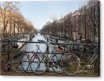 Canvas Print featuring the digital art Bikes On The Canal In Amsterdam by Carol Ailles