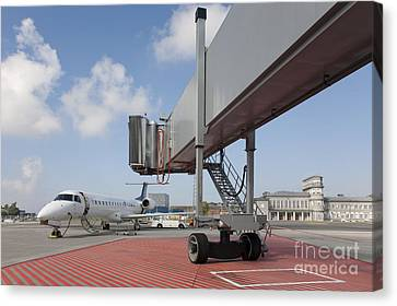 Boarding Bridge Leading To A Parked Plane Canvas Print by Jaak Nilson