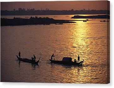 Boats Silhouetted On The Mekong River Canvas Print by Steve Raymer
