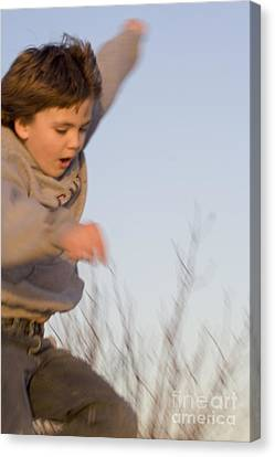 Boy Jumping Off Sand Dune Canvas Print by Christopher Purcell