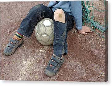 Boy With Soccer Ball Sitting On Dirty Field Canvas Print by Matthias Hauser