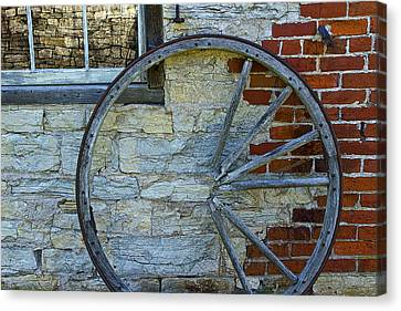 Broken Wagon Wheel Against The Wall Canvas Print by Randall Nyhof