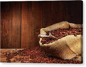 Burlap Sack Of Coffee Beans Against Dark Wood Canvas Print by Sandra Cunningham