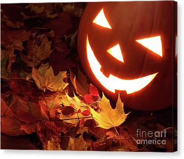Carved Pumpkin On Fallen Leaves Canvas Print