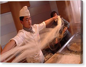Chef Stretches Dough As He Makes Fresh Canvas Print by Richard Nowitz