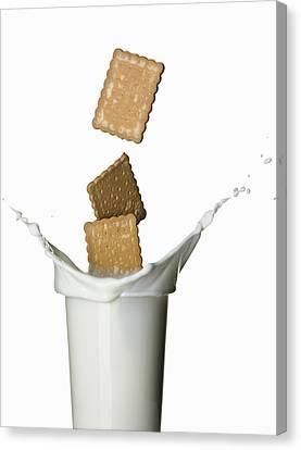 Cookies Splashing Into Glass Of Milk Canvas Print by Walter Zerla