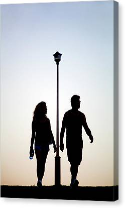 Couple Exercise While Walking At Sunset Canvas Print by Virginia Star