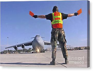 Crew Chief Marshals A C-5 Galaxy Canvas Print by Stocktrek Images