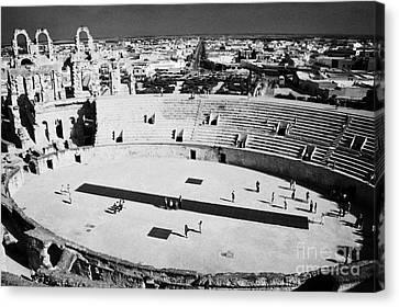 distant straight roman road leading through el Djem towards tourists the old roman colloseum arena Canvas Print by Joe Fox