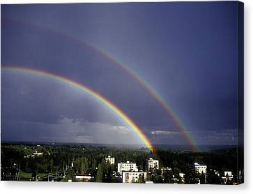 Double Rainbow Over A Town Canvas Print by Pekka Parviainen