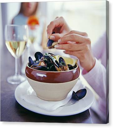 Eating Mussels Canvas Print by David Munns