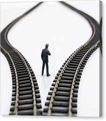 Contemplative Canvas Print - Figurine Between Two Tracks Leading Into Different Directions  Symbolic Image For Making Decisions by Bernard Jaubert