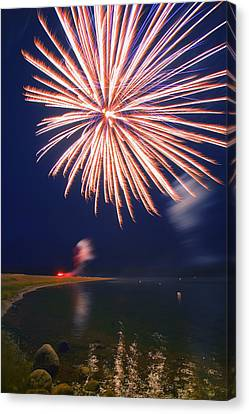 Flickering Light Canvas Print - Fireworks Over A Body Of Water by Carson Ganci
