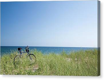 Grass Covering Bicycle Parked On Beach Dune. Canvas Print by Alberto Coto