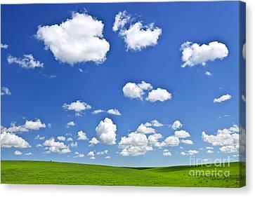 Green Rolling Hills Under Blue Sky Canvas Print