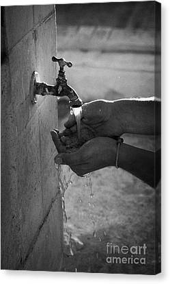 Hispanic Man Cupping Water And Washing Hands At Outdoor Tap Canvas Print by Joe Fox