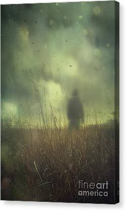 Hooded Man Walking In Field With Storm Clouds Canvas Print by Sandra Cunningham