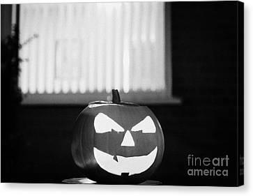 Illuminated Halloween Pumpkin Jack-o-lantern Outside The Window Of A House To Ward Off Evil Spirits  Canvas Print by Joe Fox
