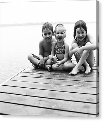 Kids Sitting On Dock Canvas Print