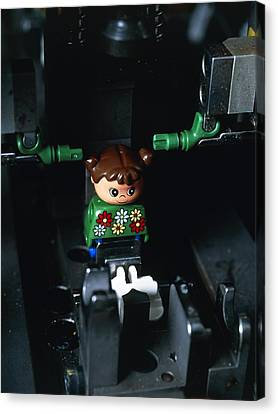Lego Doll In An Assembly Machine Canvas Print by Volker Steger