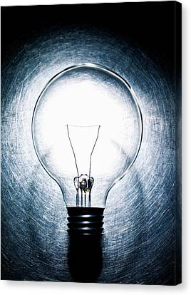 Light Bulb On Stainless Steel Background. Canvas Print by Ballyscanlon