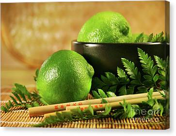Limes With Chopsticks Canvas Print by Sandra Cunningham