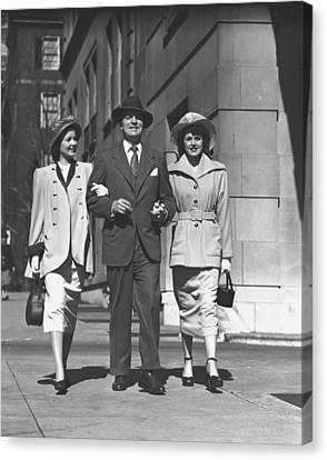 Man And Two Women Walking On Sidewalk, (b&w) Canvas Print by George Marks