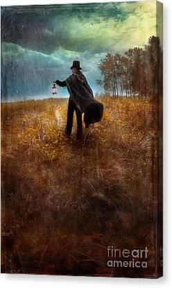 Man In Top Hat And Cape Walking In Rain Canvas Print by Jill Battaglia