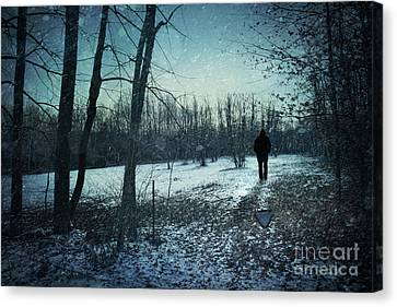 Man Walking In Snow At Winter Twilight Canvas Print by Sandra Cunningham