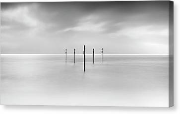 Minimal Posts Are Arranged Symmetrically In Sea Canvas Print by Doug Chinnery