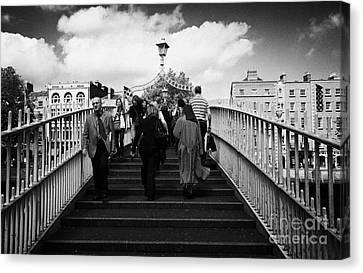 Halfpenny Bridge Canvas Print - Pedestrians Crossing The Halfpenny Hapenny Bridge Over The River Liffey In The Centre Dublin Ireland by Joe Fox