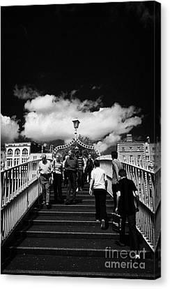 Halfpenny Bridge Canvas Print - Pedestrians Crossing The Halfpenny Hapenny Bridge Over The River Liffey In The Centre Of Dublin City by Joe Fox