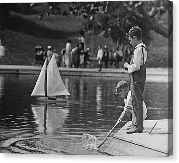 Playing With A Model Boat Canvas Print by Fpg