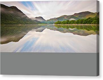 Reflection Of Mountains And Trees On Lake Canvas Print by John Ormerod