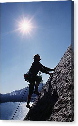 Rock Climber On Polly Dome Above Lake Canvas Print by Gordon Wiltsie